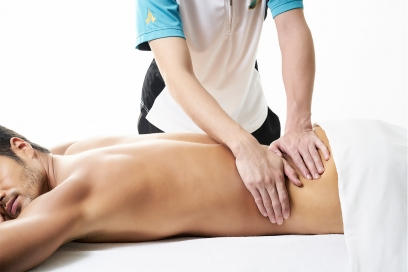Physiotherapist massage relaxing stressed lower back muscles at Chiva Som Hua Hin